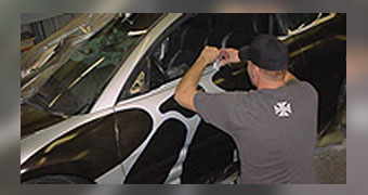Employee Applying Graphics to Side of Car - Hydrographics